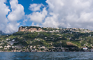 A view from the water of the Amalfi Coast of Italy, with the cliffs of Terrazza dell'Infinito above.