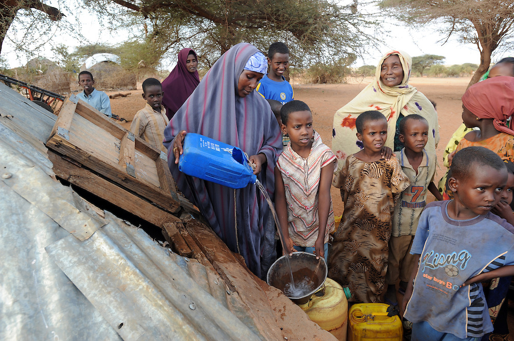 Daliabo Mohamed pouring water at the water storage tank at Belet Amin, a camp for internally displaced Somalis near the border with Kenya. The camp was set up for people fleeing the fighting in Somalia in 1997. 26/6/2008