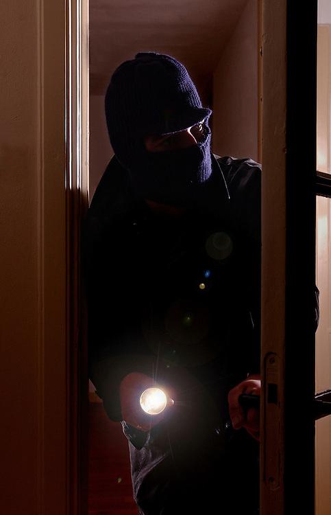 Een inbreker met bivakmuts en zaklantaarn.<br /> <br /> A burglar with a flashlight and wearing a bivac cap.