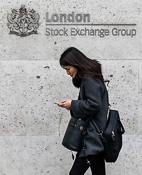 © Licensed to London News Pictures. 09/03/2020. London, UK. A City worker looks at her phone outside the London Stock Exchange today as markets around the world plunge as fears over the Coronavirus disease continues. Photo credit: Alex Lentati/LNP