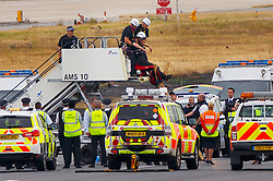© Licensed to London News Pictures. 06/09/2016. London, UK. A Black Lives Matter protester is being arrested on the runway at London City Airport in east London on Tuesday, 6 September 2016 after a group of protesters blocked runway, causing all flights in and out of the airport disrupted. Photo credit: Tolga Akmen/LNP