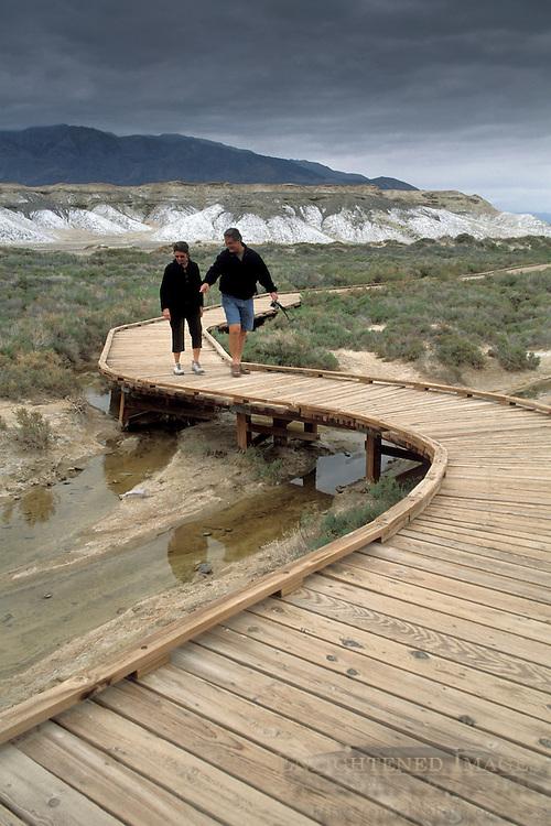Tourists walking on wooden boardwalk nature trail path at Salt Creek, Death Valley National Park, California