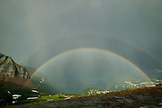 A bright double rainbow connects the mountains on both sides of Logan Pass, located in Glacier National Park, Montana. The rainbow formed as a heavy afternoon thunderstorm moved along the Going-To-The-Sun Road, which passes through the valley at the center of this image.