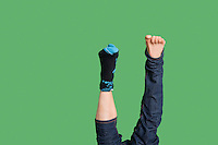 Low section of man's feet with sock in one leg over colored background