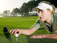 Young female golfer lying on court placing ball on tee