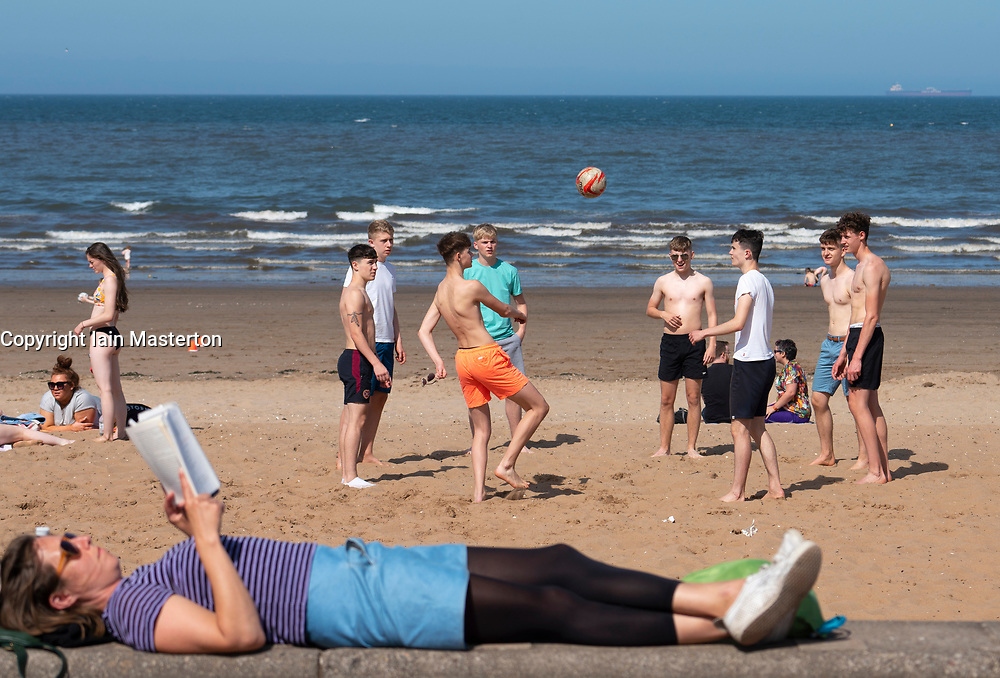 Portobello,Scotland, UK. 28 June, 2019. Warm temperatures and unbroken sunshine brought hundreds of people and families to enjoy this famous beach outside Edinburgh. Teenagers playing with football on the beach and a woman relaxing with a book.
