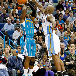 October 29, 2010; New Orleans, LA, USA; New Orleans Hornets point guard Chris Paul (3) shoots over Denver Nuggets point guard Chauncey Billups (1) during the fourth quarter at the New Orleans Arena. The Hornets defeated the Nuggets 101-95.  Mandatory Credit: Derick E. Hingle
