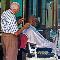Caragenas de Indias , Colombia - December 21 2010 : Colombian man getting his hair cut in an old fashioned barber shop