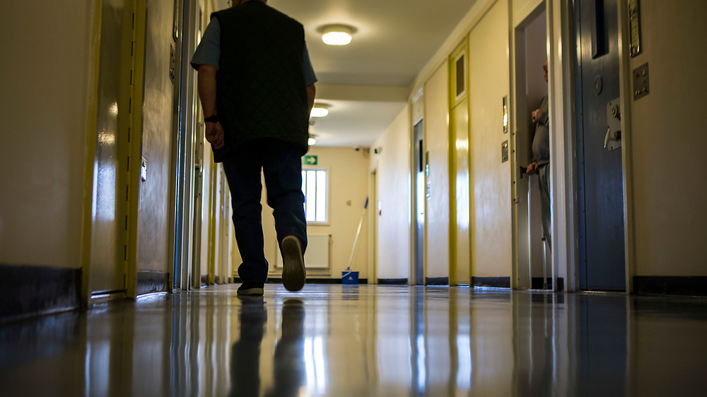 A prisoner walking down a corridor in Beaufort House, a skill development unit for enhanced prisoners. Part of HMP/YOI Portland, a resettlement prison with a capacity for 530 prisoners.Dorset, United Kingdom.