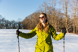 A woman snowshoeing in a field on Indian Hill in West Newbury, Massachusetts.