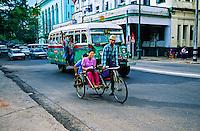 Bicycle taxi and public bus on Strand Road, Yangon (Rangoon), Burma (Myanmar)
