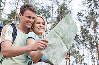 Happy young backpackers reading map in forest