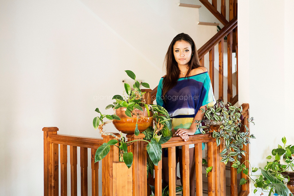 PRIOLO GARGALLO (SICILY), ITALY - 31 JULY 2013: Stefania Vincenzi, the 18 years old daughter of the missing and presumed dead Costa Concordia cruise ship passenger Mariagrazia Trecarichi, poses for a portrait by the plants left by her mother in the staircase of their home in Priolo Gargallo, Italy, on July 31st 2013. Stefania Vincenzi is running for the final selections of Miss Italy after winning the local contest in Sicily. The idea of participating at the beauty pageant came after Mariagrazia Trecarichi met a friend who organizes the local castings who told her Stefania suited the contest.<br /> <br /> Mariagrazia Trecarichi is missing since January 14th 2012, the day of her 50th birthday, after the Costa Concordia shipwrekck at the  Giglio Island in Tuscany, Italy. Of the 3,229 passengers and 1,023 crew known to have been aboard, 30 people died,, and two more passengers are missing and presumed dead, inclusding Mrs Trecarichi. Mariagrazia Trecarichi had survived two cancers and decided to celebrate her 50th birthday on the Costa Concordia.