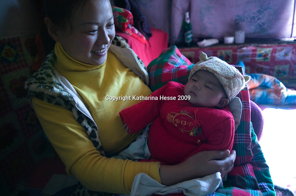 NORTHERN HEBEI PROVINCE, JANUARY 26, 2009:<br /> Mr Lu's wife smiles as she holds her newborn baby .<br /> Lu went to Beijing 8 years ago as he couldn't find a job in China's countryside.<br /> He was employed in a textile factory that went banctrupt last October. Lu and his 63 colleagues were still owed payment for 4 months, but their boss refused to pay them. They didn't know the law, nor did any of them have a contract.  <br /> At the end of January, Lu and his co-workers went to see the bosses' mother to negociate, then the union and in the end the government. They were threatened with jail . At the end of the day , a man from the union came by ( on behalf of the government )and all but an underaged worker received their due salaries.<br /> Now Lu is unemployed like 20 milion other migrant workers in China who have been laid off as a result of the financial crisis.<br /> <br /> <br /> China's Communist Party  which will celebrate its 60th anniversary in October, currently faces its biggest challenge since the beginning of the economic reforms 30 years ago  : &quot; The phase of  rapid economic growth is over. For the first time the government is threatened with a  mistrust of a wide section of the population&quot;, warns the Communist party's Shang Dewen in Beijing.   <br /> Not only the China's poorest worry about the furture, but as well China's middle class is concerned about the crisis.     1,5 Millionen university graduates didn't find a job until the end of 2008  and this summer there'll be an additional  6,1 Million new graduates. More than 12 percent of university graduates face unemployment in 2009.