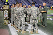 """Members of the U.S. Army take orders from their commanding officer as they stand next to a goal post decorated with an NFL military logo in honor of """"Salute to Service"""" before the Minnesota Vikings NFL week 10 football game against the Washington Redskins on Thursday, Nov. 7, 2013 in Minneapolis. The Vikings won the game 34-27. ©Paul Anthony Spinelli"""