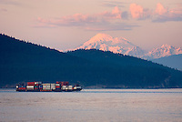 Container barge making way through Rosario Strait in the San Juan Islands, Mount Baker in the distance, Washington USA