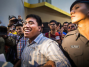 "14 FEBRUARY 2015 - BANGKOK, THAILAND: Thai police lead away a smiling Student activist Siriwit Serithiwat after they arrested during a protest the military coup. Martial law is still in effect in Thailand and protests against the coup are illegal. Dozens of people gathered in front of the Bangkok Art and Culture Centre in Bangkok Saturday to hand out red roses and copies of George Orwell's ""1984."" Protestors said they didn't support either Red Shirts or Yellow Shirts but wanted a return of democracy in Thailand. The protest was the largest protest since June 2014, against the military government of General Prayuth Chan-Ocha, who staged the coup against the elected government. Police made several arrests Saturday afternoon but the protest was not violent.      PHOTO BY JACK KURTZ"