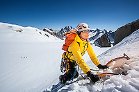 A female climber, as seen resting with ice tools embeded in a snowy slope of Pointe Lachenal on a sunny Summer afternoon in Chamonix, Mont Blanc, France.