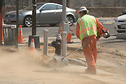 dusting the street with motorized broom at a road site construction