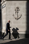Passers-by beneath a carved anchor in the Square Mile, on 6th April 2017, in the City of London, England.