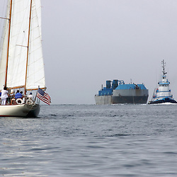 A large sailboat and a commercial tug and barge cruise near Newport , Rhode Island.