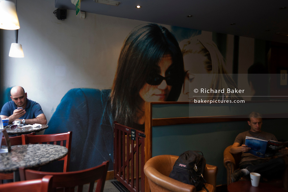 Two men sit apart in a London cafe with a background of two girlfriends chatting sd part of a wall artwork.