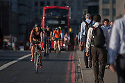 Cyclists in front of a bus, cross with commuters over London Bridge, from the City of London to the south bank of the Thames in Southwark, England UK.