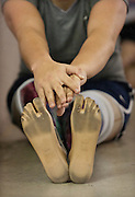 Lehi High School swimmer Amy Chapman reaches for her prosthetic toes during dry-land practice at the Lehi Legacy Center, Tuesday, Dec. 18, 2012. Chapman, 17, was born with fibular hemimelia and had both legs amputated when she was 13 months old.