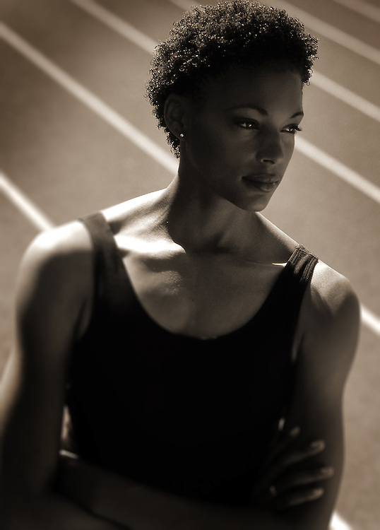 African American female athlete standing with arms crossed at track.