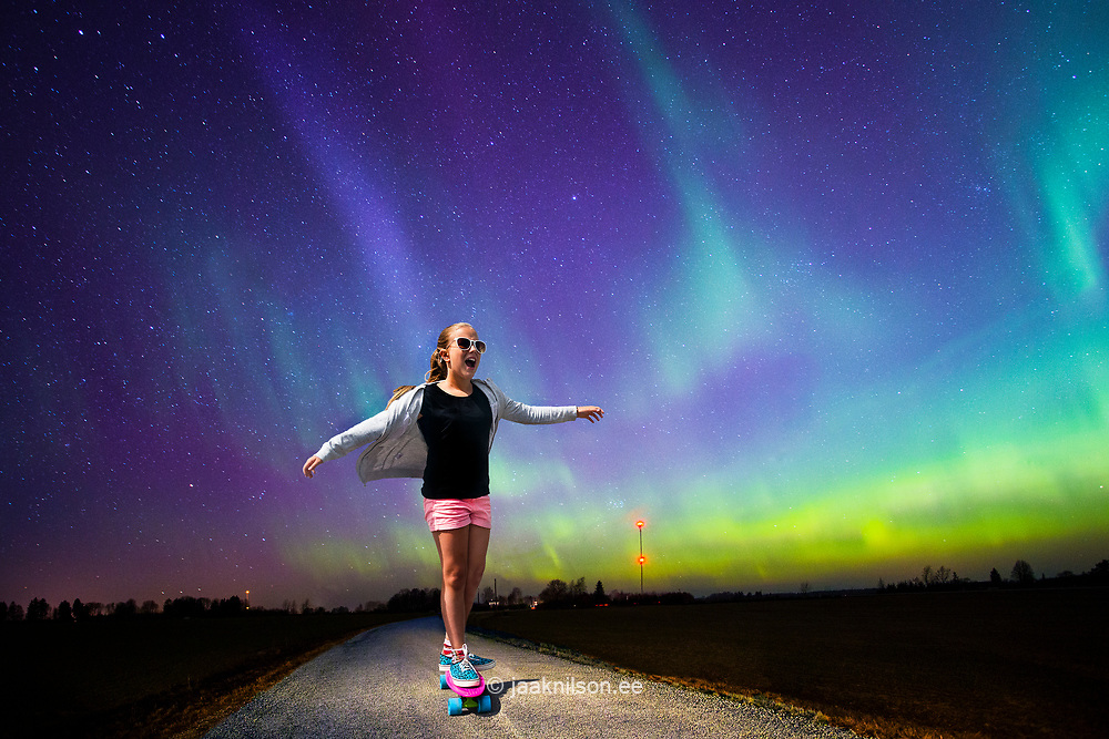 Young gilr skateboarding on road. Asphalt, Aurora Borealis. Night.