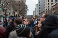A man wearing a &quot;Not My President&quot; shirt stands outside a barrier as others wait in line to pass through security to enter the inaugural parade route.<br />