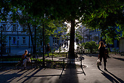 Seated on a park bench, a young Polish woman reads a book in late afternoon sunshine, on 23rd September 2019, in Krakow, Malopolska, Poland.