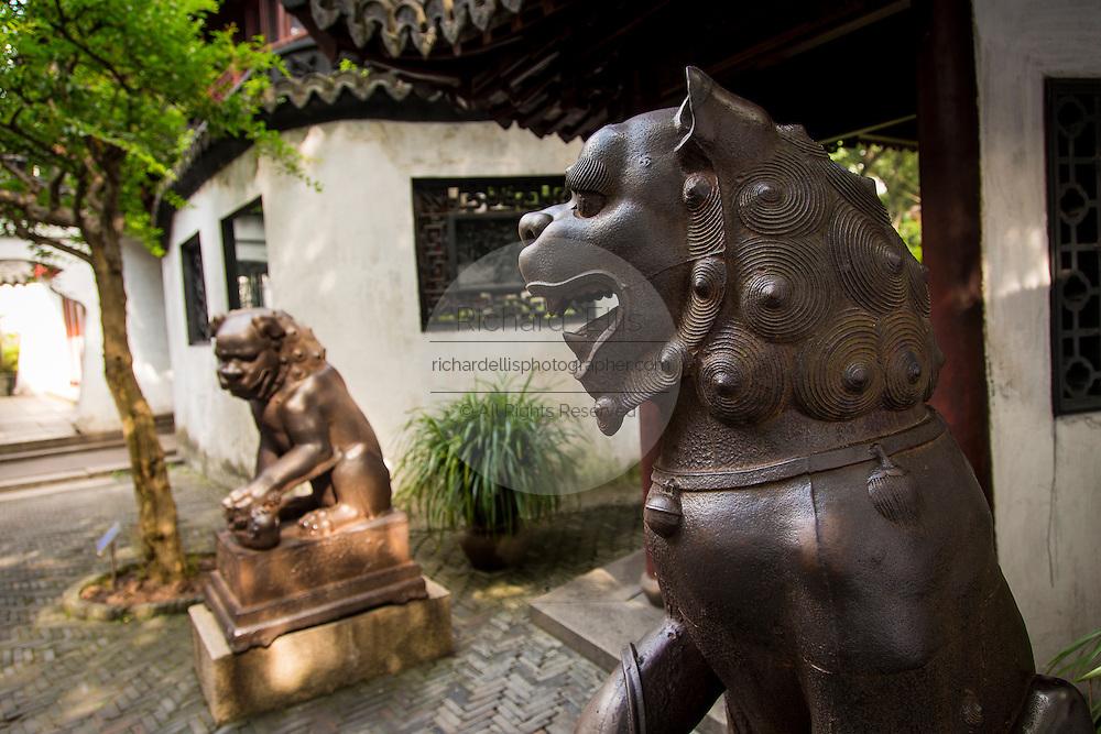 Iron lion statues guard the entry to Yu Yuan Gardens Shanghai, China