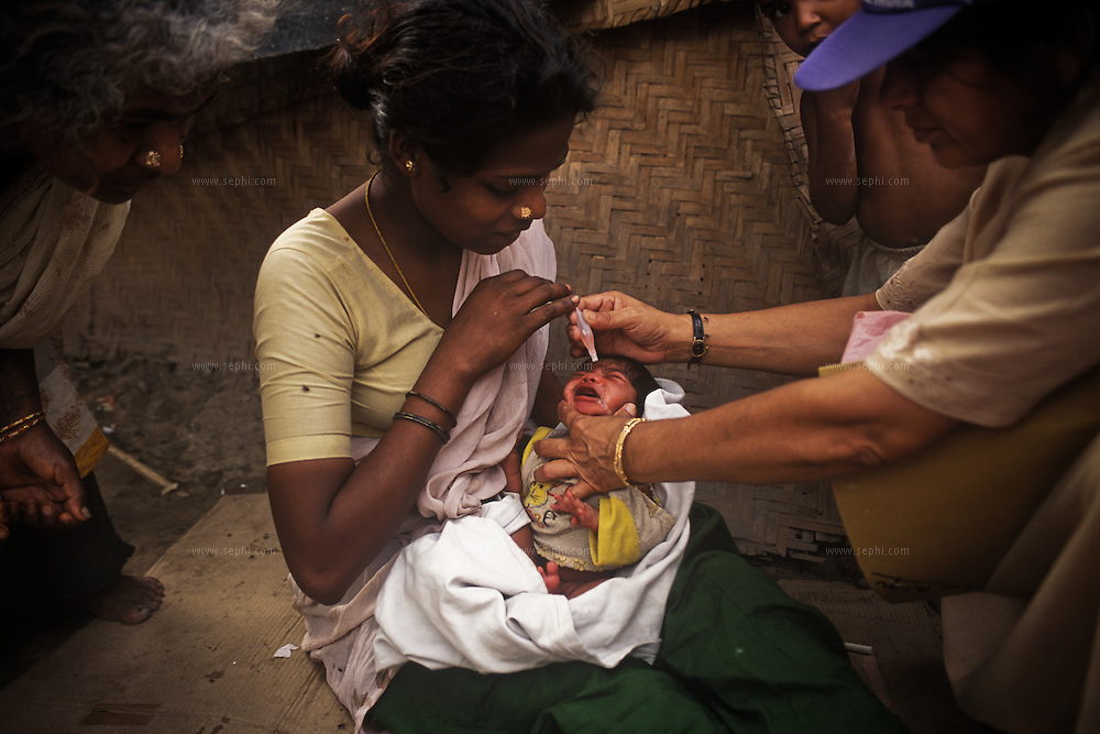 A three-days-old baby, held by his mother, is vaccinated against polio. They live in the Madrasi camp, housing immigrants from Chennai (Madras) who came to Delhi looking for employment opportunities and ended up living in shacks or Jhugis, less than two meters away from the railway tracks.