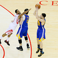 25 May 2015: Golden State Warriors guard Klay Thompson (11) takes a jump shot over Houston Rockets forward Trevor Ariza (1) off a screen set by Golden State Warriors center Andrew Bogut (12) during the Houston Rockets 128-115 victory over the Golden State Warriors, in game 4 of the Western Conference finals, at the Toyota Center, Houston, Texas, USA.