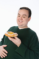 Overweight mid-adult man holding pastry