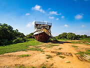 31 MAY 2016 - SIEM REAP, CAMBODIA:  The Tara is a river freighter and passenger boat assembled in Vietnam, then a French colony, in 1927. Most recently it's used to take tourists on dinner cruises on the Tonle Sap Lake. Because of the drought in Cambodia, the Tara is beached and unable to navigate the nearly empty canals that lead to the Tonle Sap Lake. The boat's owners are repairing and refurbishing it while it's beached and hope that the coming rainy season will flood the canal enough to let the Tara get back to the lake.    PHOTO BY JACK KURTZ