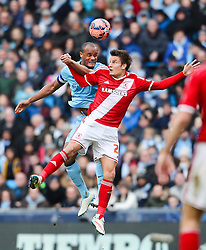 Middlesbrough's Patrick Bamford challenges Manchester City's Vincent Kompany for a header - Photo mandatory by-line: Matt McNulty/JMP - Mobile: 07966 386802 - 24/01/2015 - SPORT - Football - Manchester - Etihad Stadium - Manchester City v Middlesbrough - FA Cup Fourth Round