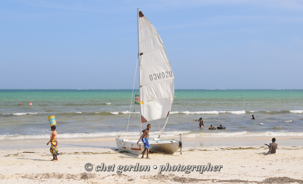 Young boy with a catamaran in the surf at Bamburi Beach in Mombasa, Kenya on Thursday, December 8, 2011.