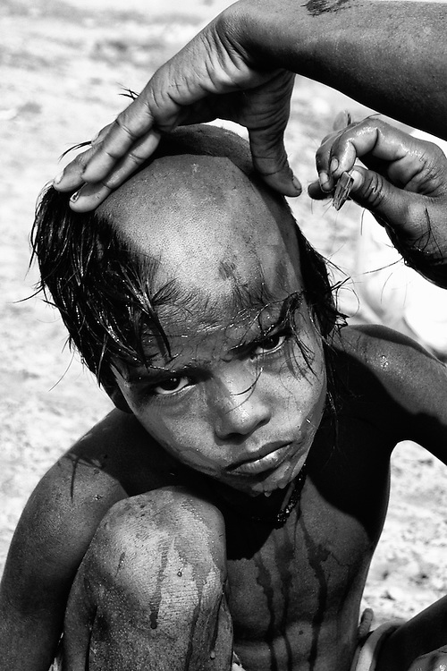 A young boy in Varanasi (Uttar Pradesh, India) shaves of his hair before the cremation ceremony, to be held later that day.