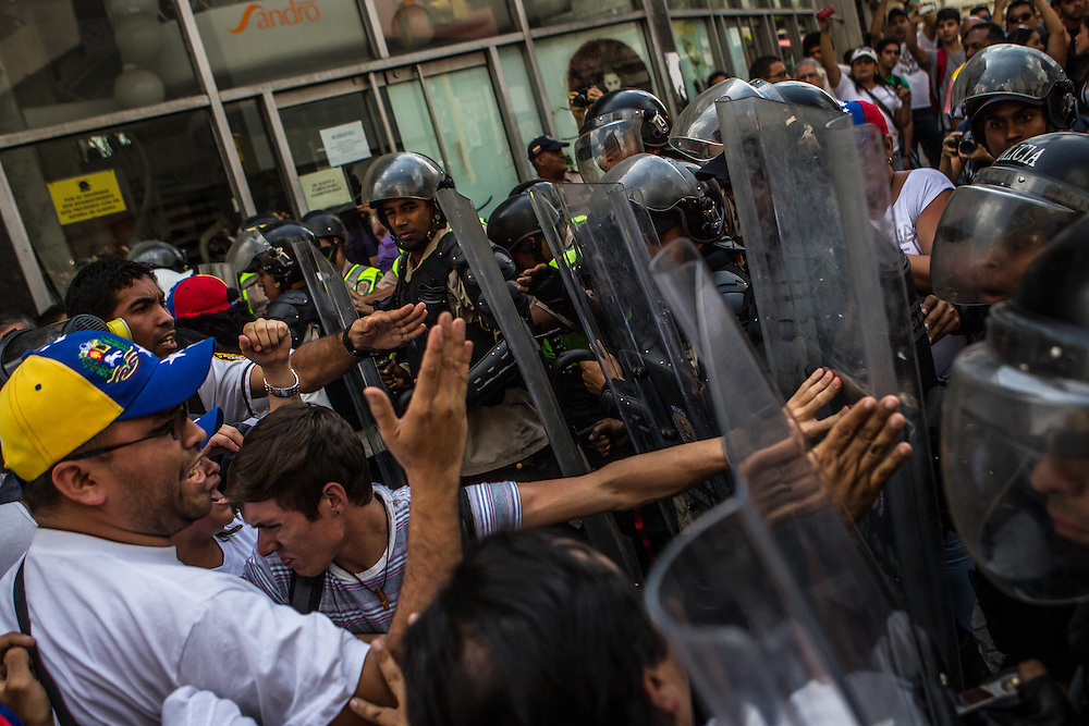 CARACAS, VENEZUELA - FEBRUARY 18, 2014:  Lopez supporters clash with riot police in effort to block the path of the armored vehicle carrying Leopoldo Lopez after he surrendered to the police. The government has said López is responsible for inciting recent street protests, that have killed three people. CREDIT: Meridith Kohut for Bloomberg News