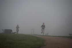 © London News Pictures. 16/10/2013. London, UK.   Runners in thick fog on Parliament Hill in Hempstead, North London. Parts of the UK have woken to thick fog this morning. Photo credit: Ben Cawthra/LNP