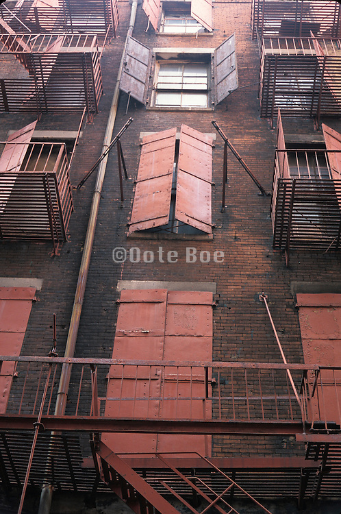 Vertical view of windows with rusty metal doors