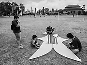 01 AUGUST 2017 - UBUD, BALI, INDONESIA: Kite flyers prepare to fly their bebean (fish shaped) kite on the public school soccer field in Ubud. Kite flying is a popular past time on Bali. It originally had religious connotations, it was used to ask the gods for bountiful rains and harvests. The kites are large. Small ones, flown by individuals are about two meters long, larger ones flown by teams of up to 80 people are ten meters long. There are three shapes of traditional kites, bebean (fish-shaped), janggan (bird-shaped) and pecukan (leaf-shaped). The pecukan is the most unstable and difficult to fly.    PHOTO BY JACK KURTZ