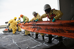 Relief workers cleaning an oil covered boom.