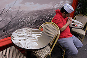 Chef relaxes at a table picturing the ancient ruins of Gerrha, in front of a panorama of the Bekaa Valley in Lebanon outside a Lebanese cafe in London's Soho.