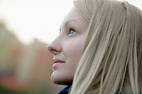 Profile of blonde woman outside looking up