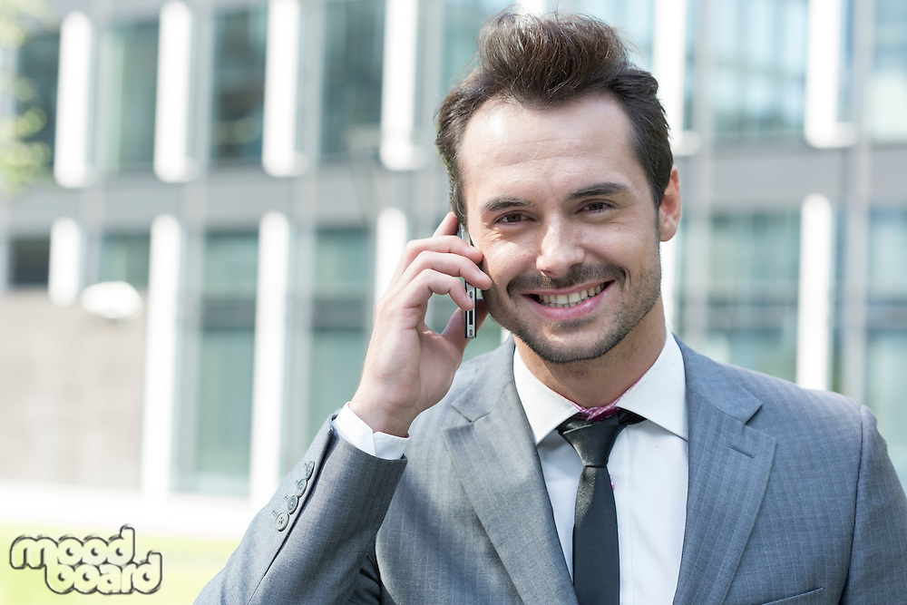Portrait of happy businessman using cell phone outside office