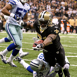 2009 December 19:  New Orleans Saints running back Mike Bell (21) dives past Dallas Cowboys cornerback Orlando Scandrick (32) for a touchdown in the fourth quarter during a 24-17 win by the Dallas Cowboys over the New Orleans Saints at the Louisiana Superdome in New Orleans, Louisiana.