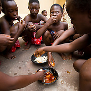 Young girls from the Krobo tribal group eat boiled yam and tomato sauce, a traditional local dish, as they undergo puberty rites - locally called dipo - in Somanya, Eastern Region, Ghana.